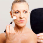 middle aged woman applying makeup on her face