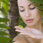 Beautiful caucasian woman holding natural aloe vera facial gel skin care and wellness. Facial moisturize mask spa salon outdoors.
