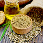 Hemp Flour in a wooden bowl hemp seed in a bag and on the table hemp oil in a glass jar hemp leaf and bread on a wooden boards background