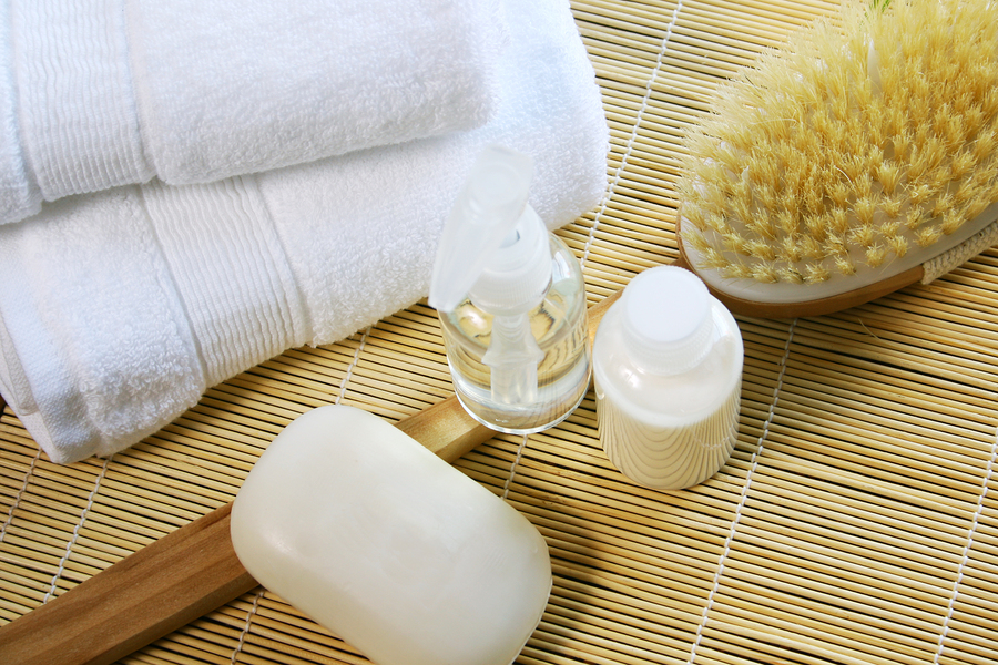 Skin care products crea oil soap brush and towels on a bamboo doily