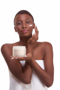 woman putting on skin cream